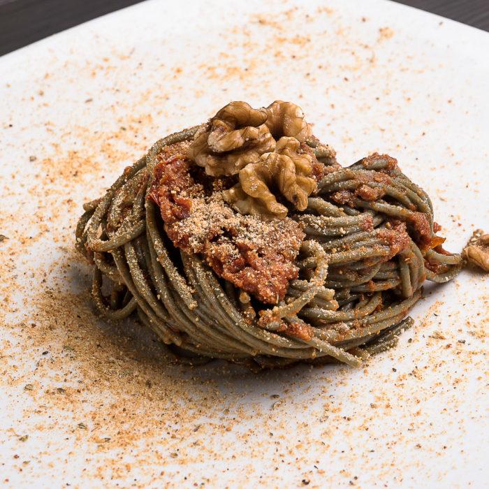 spaghetti neri con pesto di pomodori secchi, capperi e noci